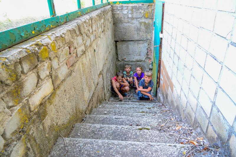 Children in the basement, three boys and a girl near the iron door are hiding on the steps from the outside world. Post-production. Photo stock images