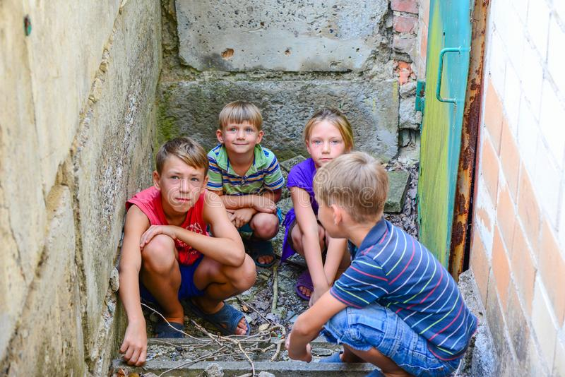 Children in the basement, three boys and a girl near the iron door are hiding on the steps from the outside world. Post-production. Photo stock image