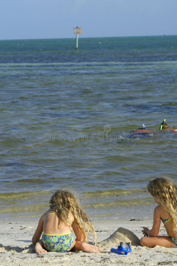 Children at the beach with divers stock photos