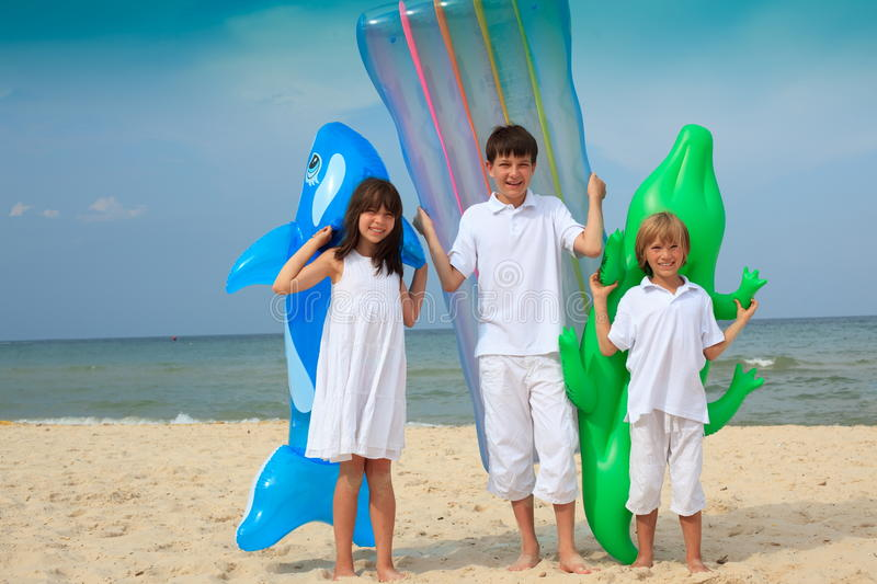 Children on beach with inflatables. Two young boys and girl on beach with inflatable mattresses, sea in background royalty free stock photos