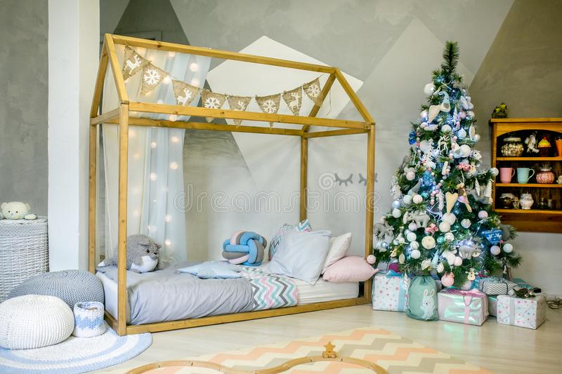 Children bedroom decorated for Christmas. Big wooden frame bed with pillows and plush toys, Christmas tree with balls, ribbons and stock photo
