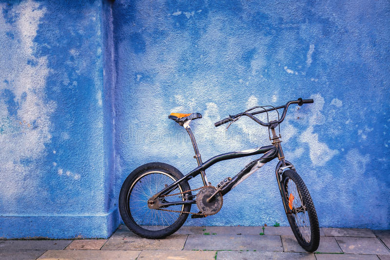 Children bicycle on blue wall royalty free stock image