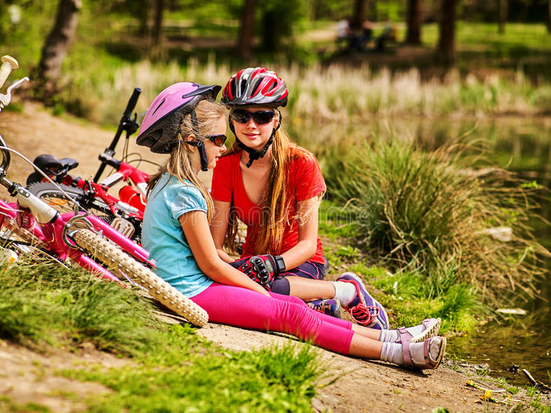 Children bicycle have rest near water in park outdoor. Bikes cycling children. Girl rides bicycle. Kids have rest near water in park. Bicycles are on coast stock photos