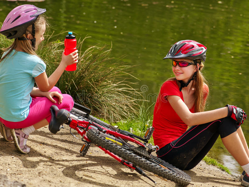 Children bicycle have rest near water in park outdoor. Bikes cycling children. Happy children rides bicycle. Children have rest near water in park. Bicycles are royalty free stock photo