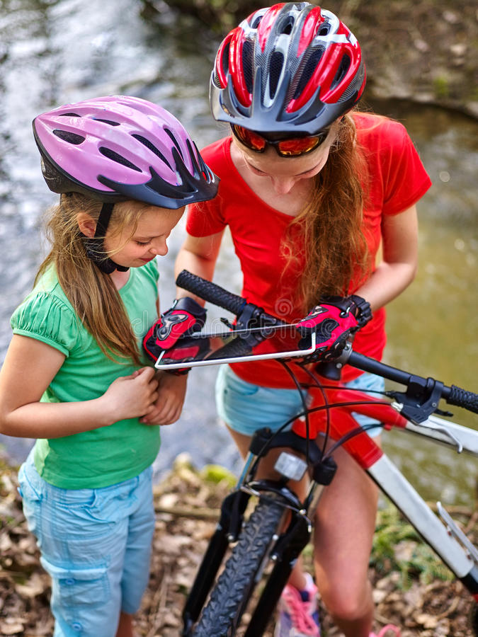 Children bicycle with tablet PC searching way into internet map. Bikes cycling girls. Girls children with tablet PC rides bicycle and searching way into stock photography