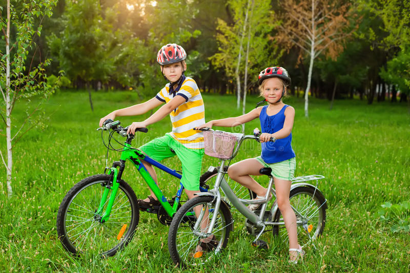 Children on bicycles in a field of grass. Healthy lifestyle royalty free stock photography