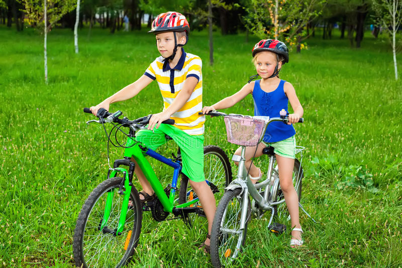 Children on bicycles in a field of grass. Healthy lifestyle royalty free stock photo