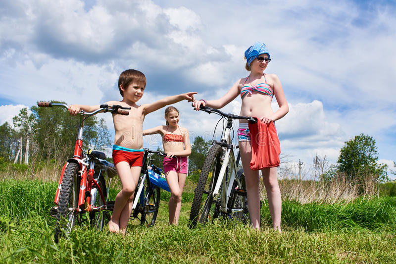 Children with bicycles outdoors on sunny day. Children with bicycles outdoors on a sunny summer day royalty free stock photo