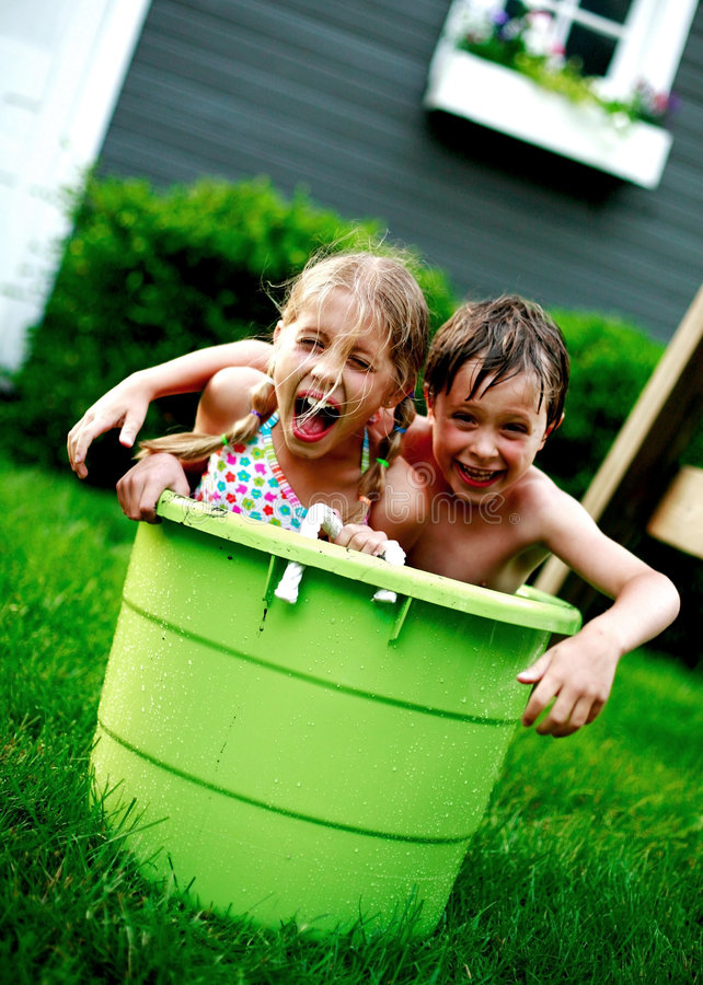 Children in big green bucket stock images