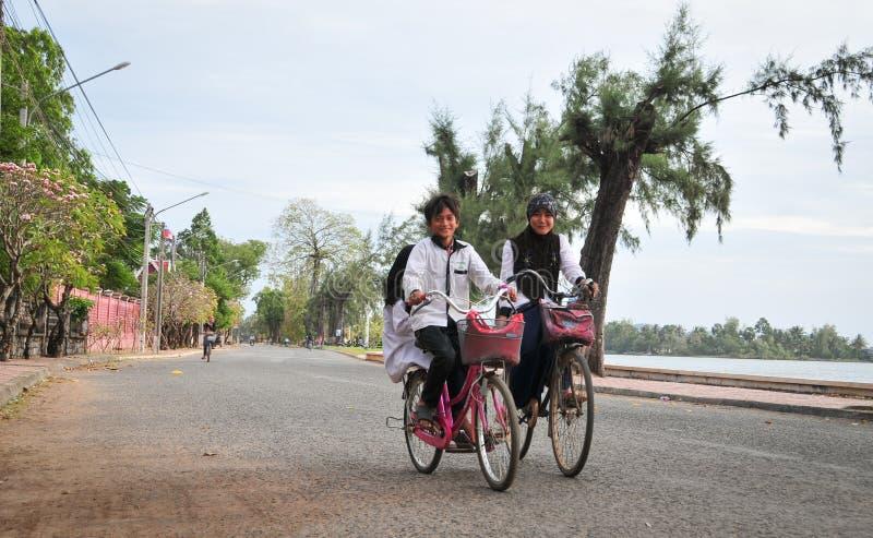 Children biking on street in Kampot, Cambodia royalty free stock image