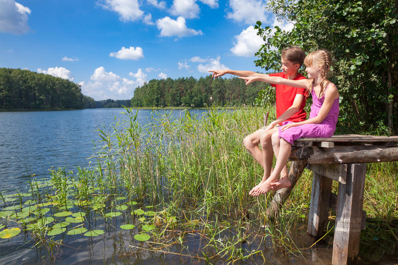 Children birdwatching at a summer lake stock images