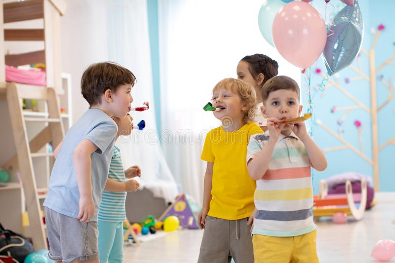 Children birthday party. Kids blow noisemaker horns royalty free stock images