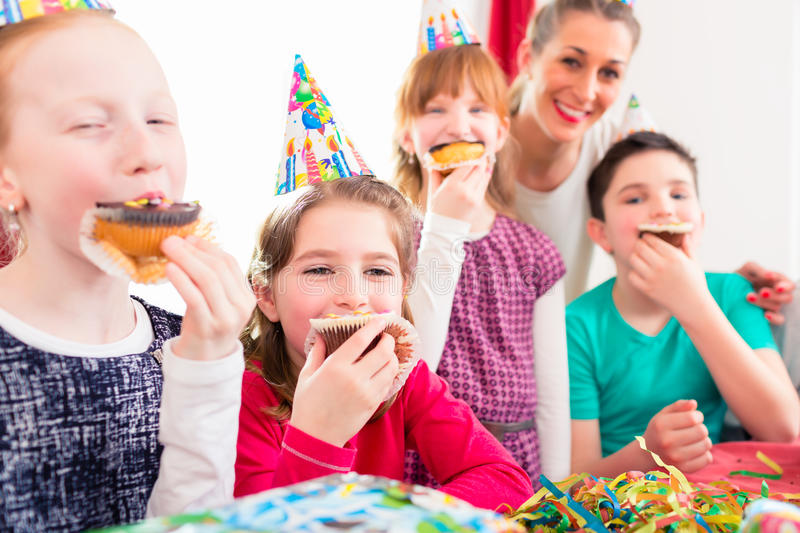 Children at birthday party with muffins and cake. Children grabbing muffins at birthday party and cake, the kids are wearing hats, balloons and paper streamers stock photos