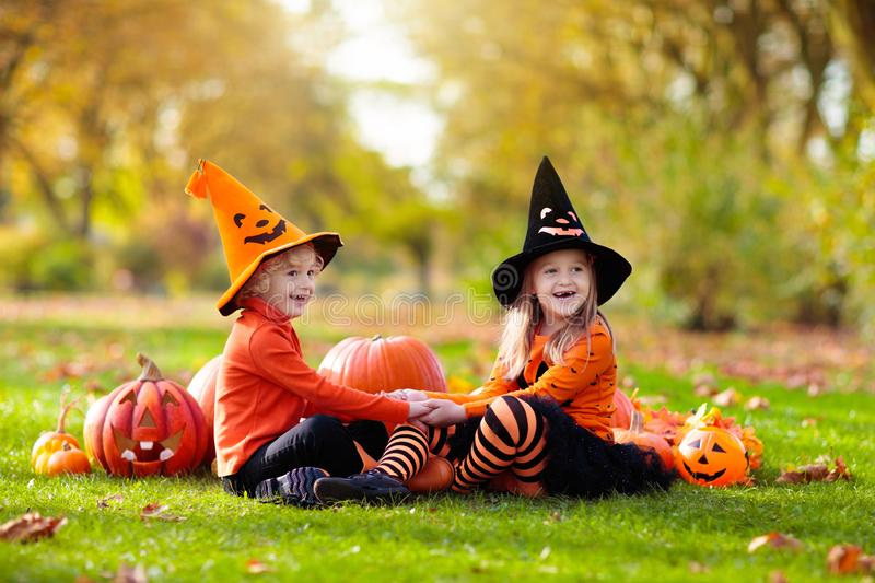 Kids with pumpkins in Halloween costumes royalty free stock photo