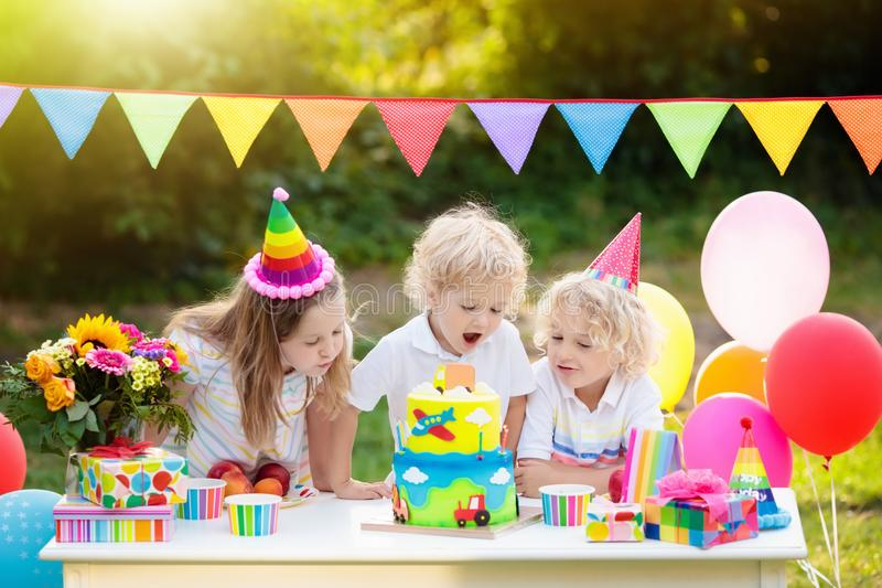Children blow candles on birthday cake. Kids party. Decoration and food. Boy and girl celebrating birthday of little brother. Transport and car kid event theme royalty free stock photos