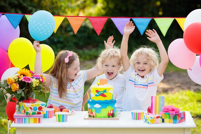Children blow candles on birthday cake. Kids party. Decoration and food. Boy and girl celebrating birthday of little brother. Transport and car kid event theme royalty free stock image