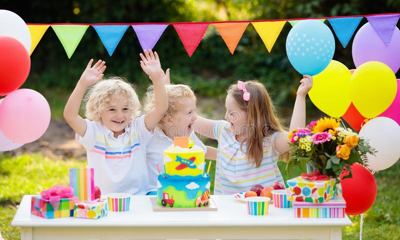 Children blow candles on birthday cake. Kids party. Decoration and food. Boy and girl celebrating birthday of little brother. Transport and car kid event theme royalty free stock photography