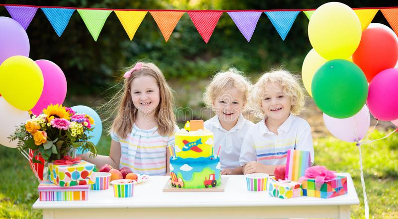 Children blow candles on birthday cake. Kids party. Decoration and food. Boy and girl celebrating birthday of little brother. Transport and car kid event theme stock image