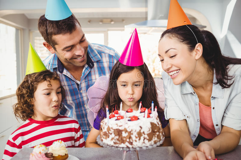Children blowing candles on birthday cake stock images