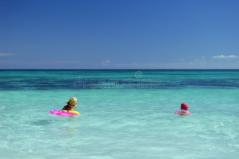 Children in a blue ocean. Two children with inflatable toys in a clear blue ocean royalty free stock photo