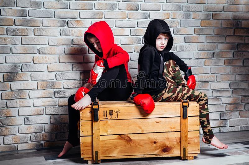 Little twin brothers dressing in sportswear wearing boxing gloves posing in a studio. stock photos