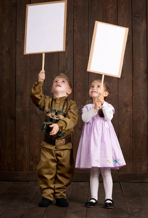 Children boy are dressed as soldier in retro military uniforms and girl in pink dress. They`re holding blank posters for veterans stock images