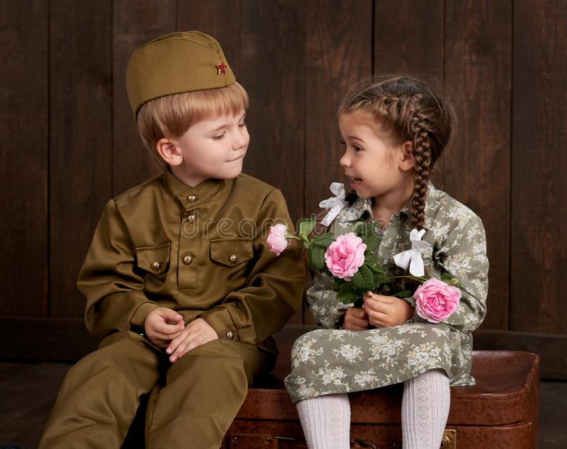 Children boy are dressed as soldier in retro military uniforms and girl in pink dress sitting on old suitcase, dark wood backgroun. D, retro style royalty free stock photography
