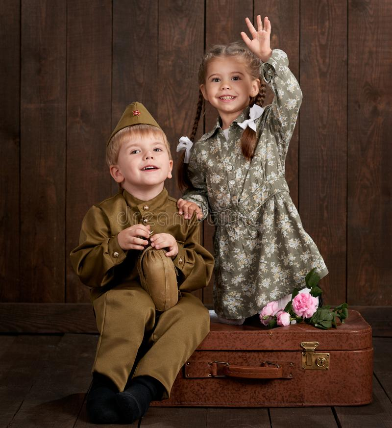 Children boy are dressed as soldier in retro military uniforms and girl in pink dress sitting on old suitcase, dark wood backgroun. D, retro style stock images