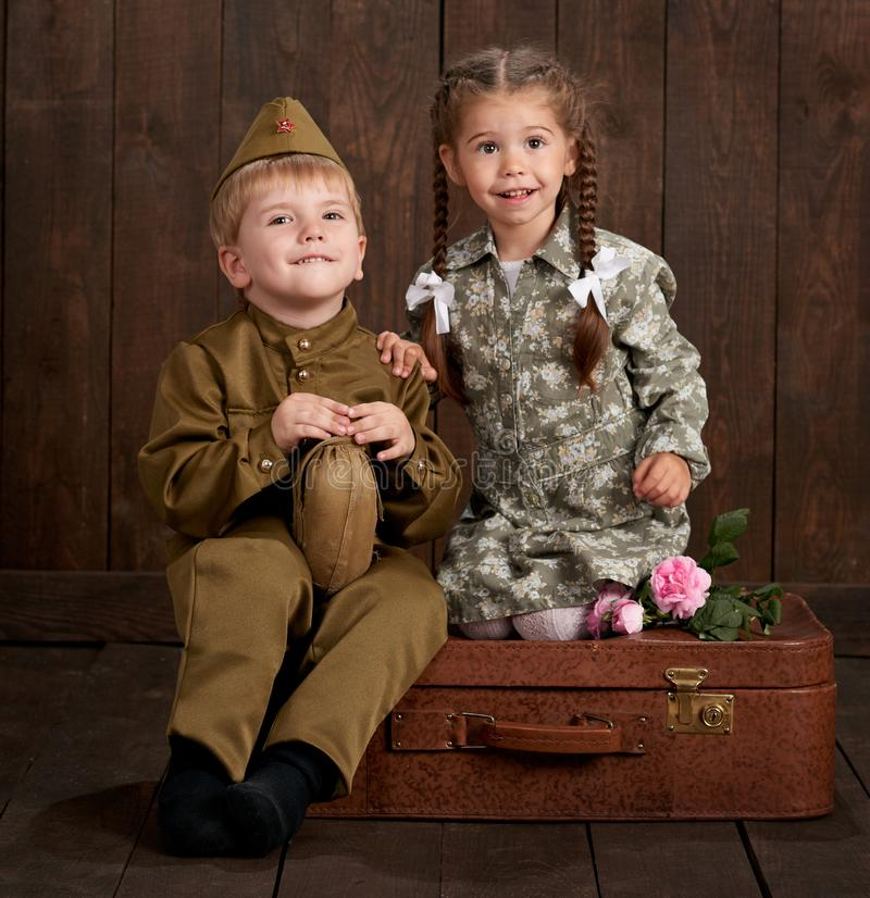 Children boy are dressed as soldier in retro military uniforms and girl in pink dress sitting on old suitcase, dark wood backgroun stock photo