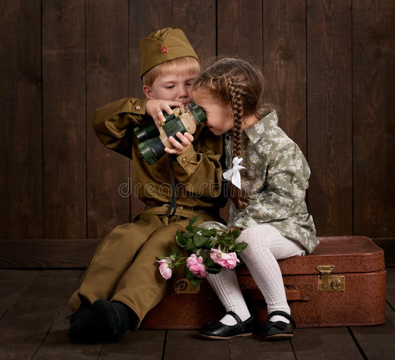 Children boy are dressed as soldier in retro military uniforms and girl in pink dress sitting on old suitcase, dark wood backgroun. D, retro style stock image