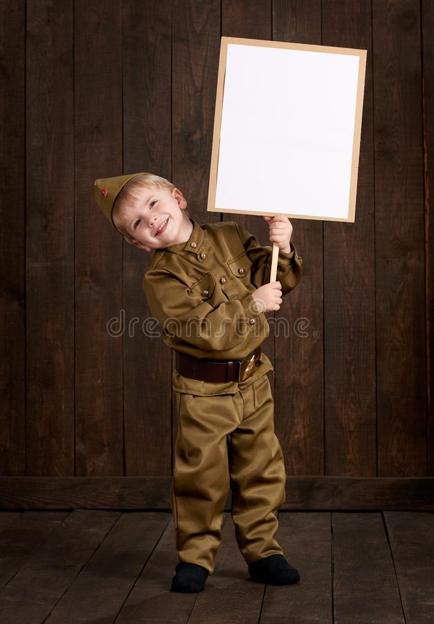 Children boy are dressed as soldier in retro military uniforms. He holds blank poster for veterans portrait. royalty free stock photo