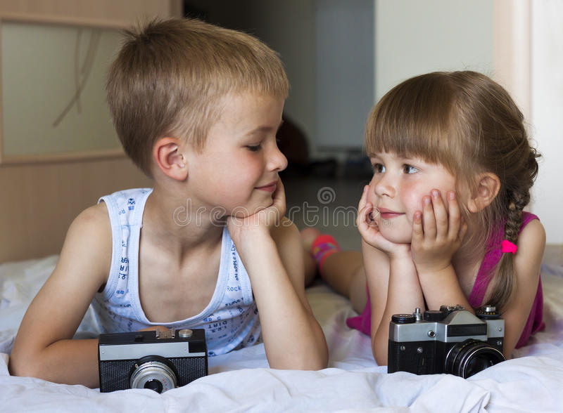 Children boy and girl brother and sister playing with cameras lo. Oking at each other. Family relations concept stock photography
