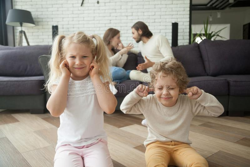 Children boy and girl covering ears, parents arguing at backgrou stock images