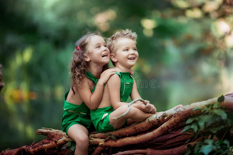 Children a boy and a girl in the forest near a fabulous green lake sitting on a fallen tree.  royalty free stock photo
