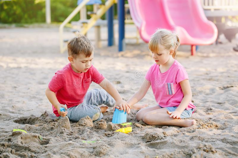 Children boy and girl friends preschoolers playing with sand and toys in sandbox on summer day royalty free stock photo