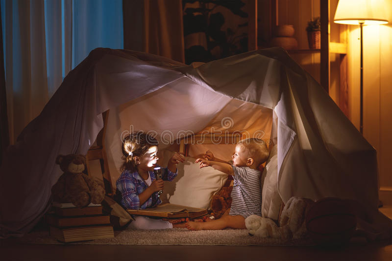 Children boy and girl playing and frighten each other in tent. Children boy and girl playing and frighten each other with flashlight in tent at night stock photos