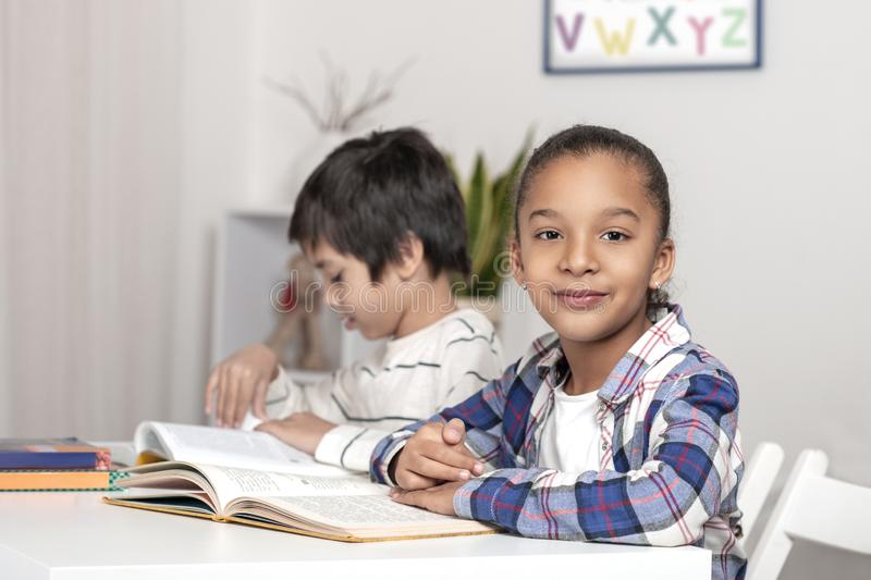 Children, boy and girl, sit at the table and read books or textbooks. The mulatta girl is looking at the camera and smiling royalty free stock photography
