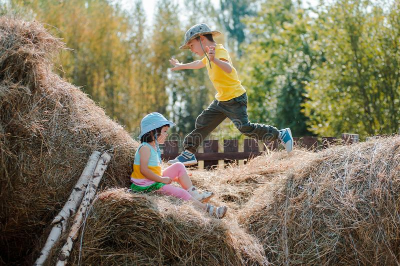 Children boy and girl on summer vacation frolic jumping on the village hayloft. royalty free stock photos