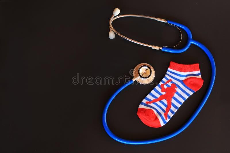 Children boy socks and stethoscope, symbolizing children healthcare / pediatric care. On a black background royalty free stock photos