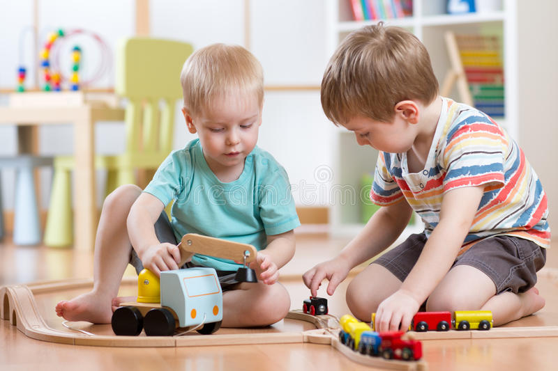 Children boys playing railroad together in playroom stock photography