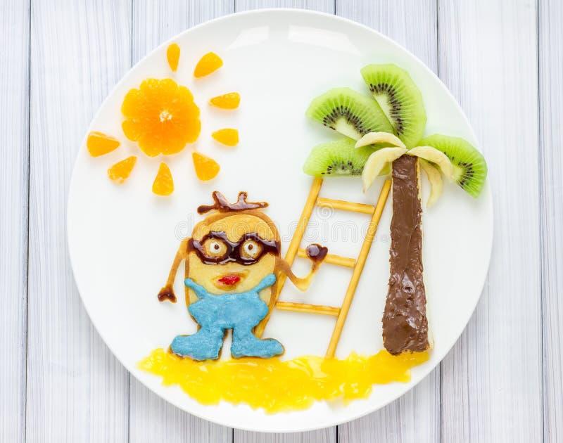 Children breakfast with pancakes and fruits. Cartoon hero. stock photos