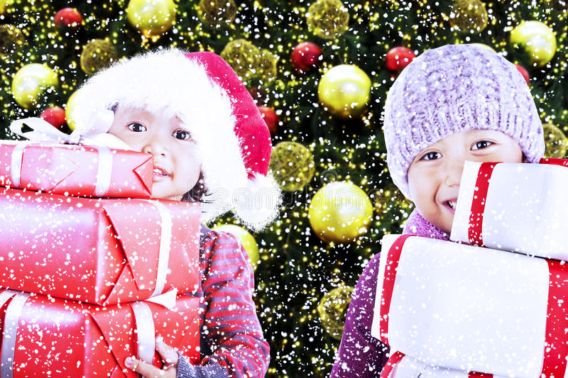 Download Children Bring Christmas Gifts Under Tree Stock Images - Image: 27920324