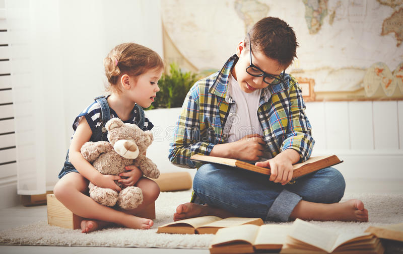 Children brother and sister, boy and girl reading a book stock images