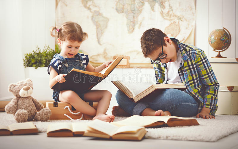 Children brother and sister, boy and girl reading a book royalty free stock photo