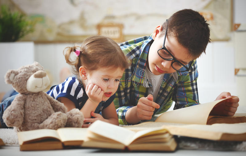 Children brother and sister, boy and girl reading a book stock photography