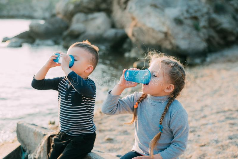 Children, brother and sister at sea drink from plastic blue cups of water or juice stock photography