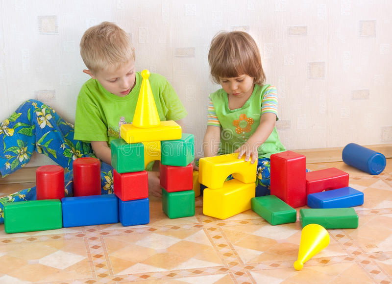 Children build a tower of cubes. In an interior royalty free stock image