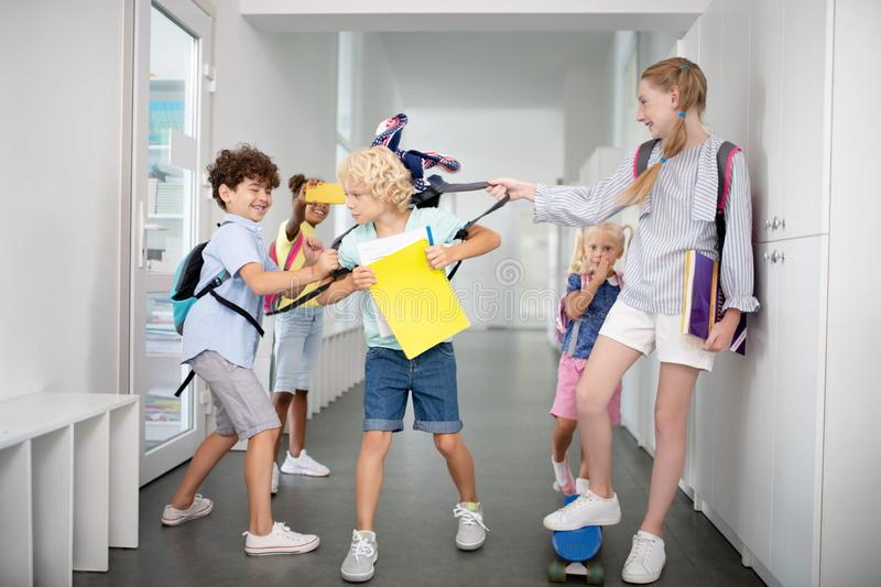 Children bullying poor boy while taking his backpack and pushing. Children pushing. Rude children bullying poor blonde boy while taking his backpack and pushing stock photos