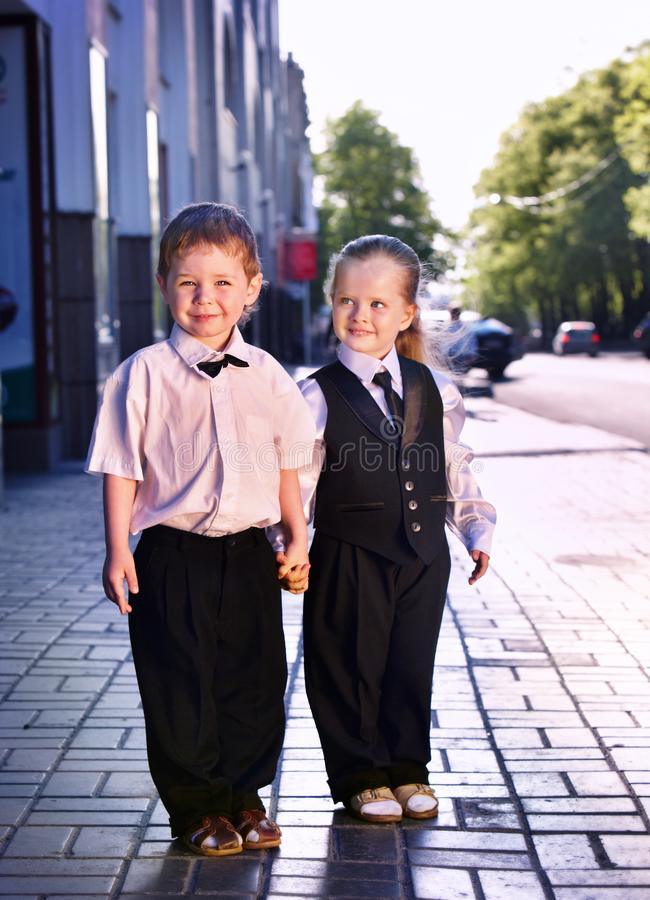 Children in business suits in center outdoor city street. royalty free stock photography