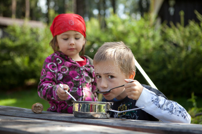 Children camping. Two children camping and having a lunch outdoors royalty free stock photography